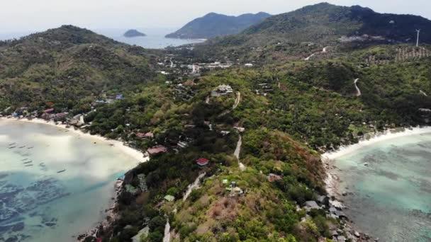 Bungalók és zöld pálmák a trópusi strandon. Nyaralók a homokos parton a búvárkodás és snorkeling üdülőhely Koh Tao paradicsomi sziget közelében nyugodt kék tenger napsütéses napon Thaiföldön. Drone nézet.