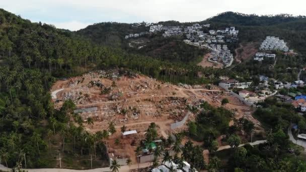 Tropisches Terrain mit gefährdeten Wäldern und Luxusvillen. Drohnenaufnahme großer Tropen mit Störungen des Ökosystems durch Gebäude und Abholzung. Koh Samui. Kokospalmenplantagen.