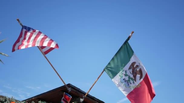 Mexická trikolóra a americká vlajka vlající ve větru. Dvě národní ikony Mexika a Spojených států proti obloze, San Diego, Kalifornie, USA. Politický symbol hranic, vztahu a sounáležitosti