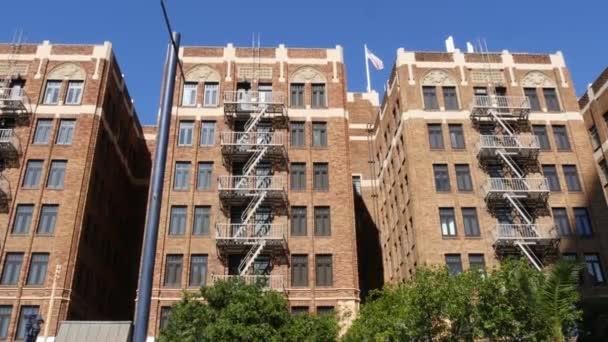 Požární žebřík před obytnou cihlovou budovou v San Diegu, USA. Typický New York nouzový východ pro bezpečnou evakuaci. Klasický retro dům exteriér jako symbol nemovitostí