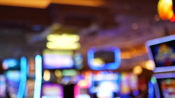 Defokussierte Spielautomaten glühen im Casino auf dem fabelhaften Las Vegas Strip, USA. Verschwommene Glücksspiel-Jackpot-Spielautomaten in einem Hotel in der Nähe der Fremont Street. Leuchtende neonfarbene Spielautomaten für Risikospiele und Wetten