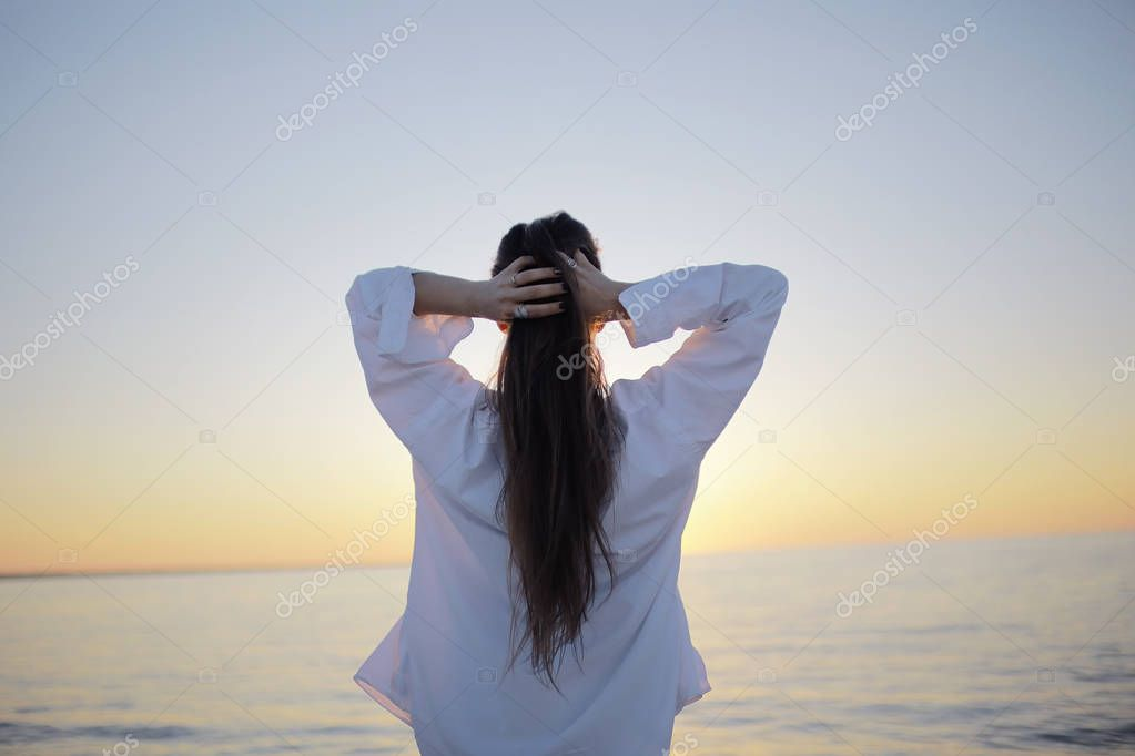 young woman looking at sea, back view, concept of freedom and happiness