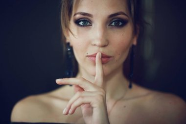 girl holding finger on mouth