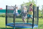 tři malé dívky sestry skákání na trampolíně venku v létě