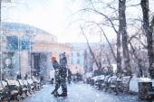 Fotografie young man and woman walking in winter city, romantic happy couple