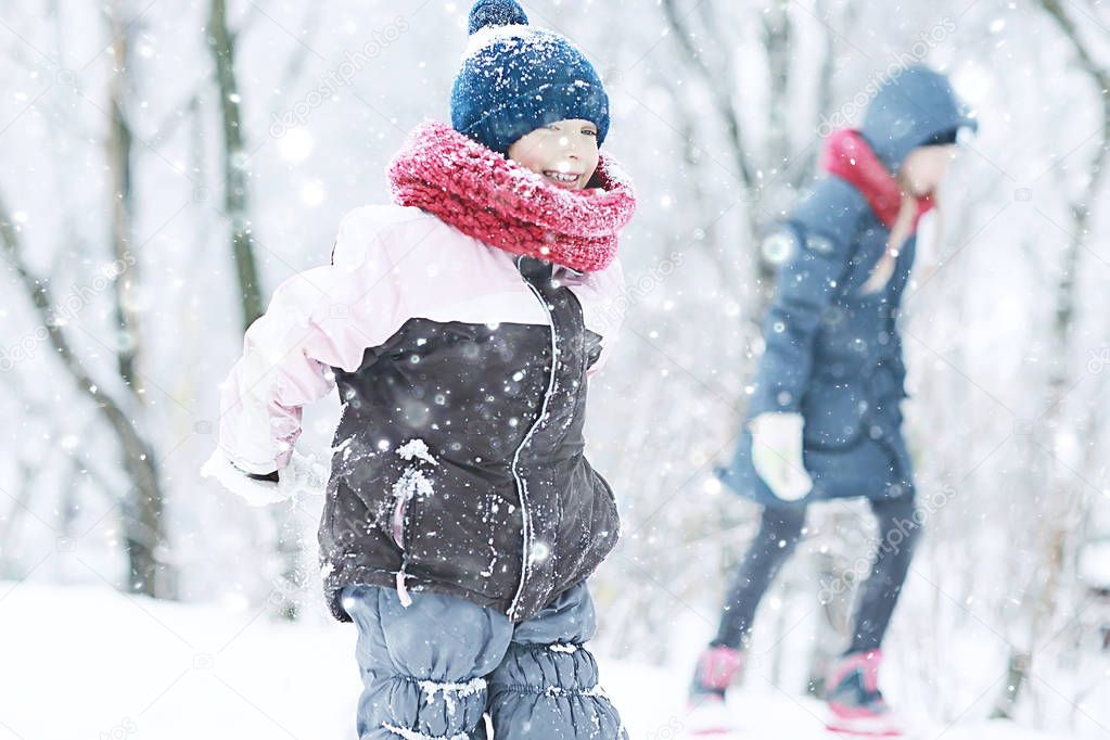 two little girls playing with snow in winter park. The concept of childhood, friendship, family
