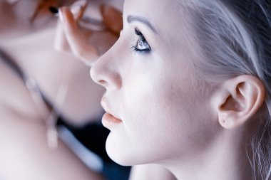professional make-up in the beauty salon.  Master doing make-up for beautiful model in the salon
