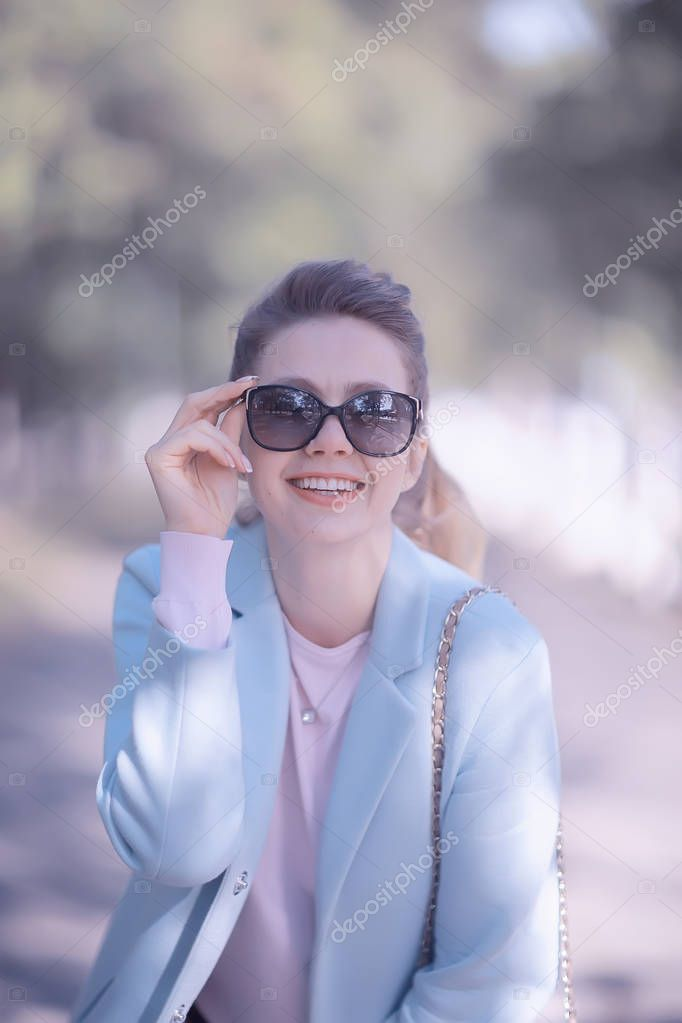 portrait of beautiful young woman wearing sunglasses in spring park