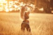 Mladá krásná žena s dlouhými vlasy, působícím na poli ovesných, letní prázdniny