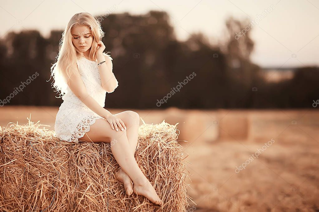 beautiful young woman in rural field at sunset, summer vacation