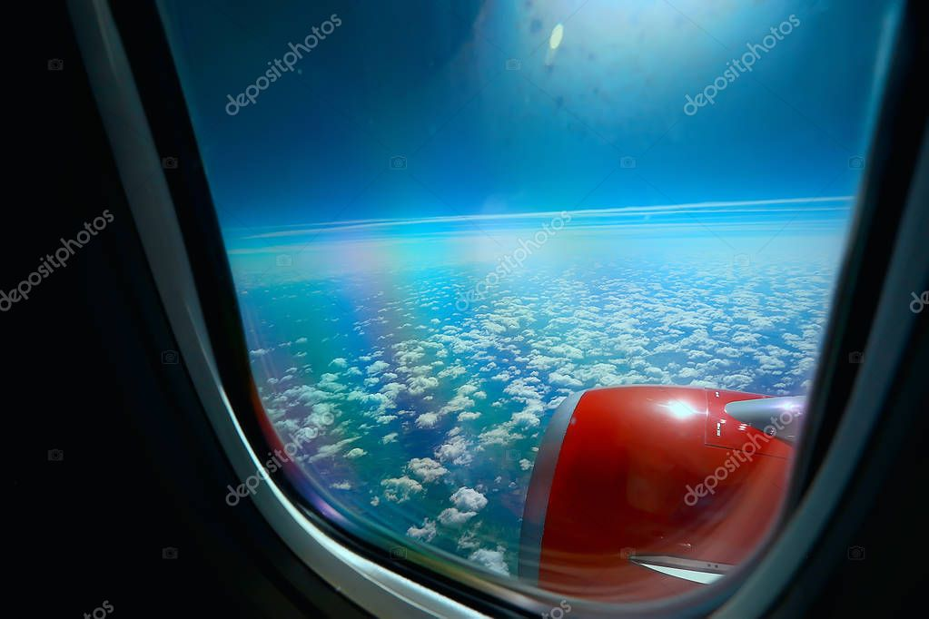 aerial view of land and wing of airplane, view from the cabin of an airplane, concept of air transport