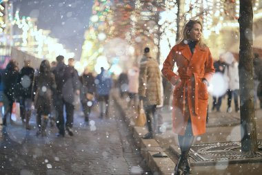 Christmas walk in city / adult girl walks in the night city on a festive night, the lights of city are new year