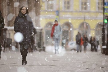 adult model girl in a coat on a winter walk in the city / Christmas vacation city tour