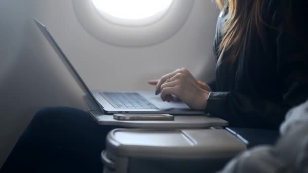 Busy lady using modern laptop in airplane