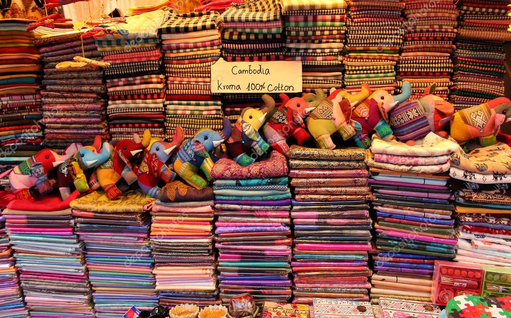 SIEM REAP, CAMBODIA - Mart 22, 2018: Kroma or krama (scarf) cotton khmer cloths for sale at a market. Cambodian souvenirs - scarves and toy elephants made of textiles are very popular with travellers