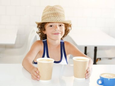 A child standing by the bar counter of a cafe and taking two cups of coffee