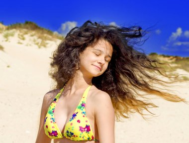 Outdoor fashion photo of beautiful happy woman at sea. Beach travel. Summer vibes. stylish girl in a yellow swimsuit standing with flying hair from the wind on the beach