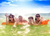 Fotografie Happy family of four in vacation at sea shore. Happy family with yellow mattress bathes in sea. happy mum daddy and two children play in water