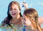 Fotografie zwei glückliche Kinder, die tagsüber auf dem Schwimmbad im Aquapark spielen. Menschen, die Spaß im Freien haben. Konzept des freundlichen Familien- und Sommerurlaubs.