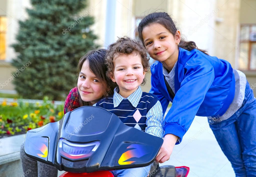 Kids driving electric toy car in summer park. Outdoor toys. Children in battery power vehicle. Little boy and his two older sisters are riding a toy truck in the city. Affection and fun time concept
