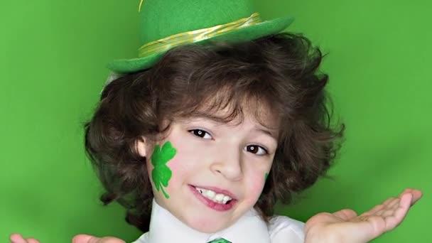 Kind, das den Patrick s Day feiert und in die Kamera blickt. Ein kleiner, kurviger Junge mit Zeichnung in Form eines Kleeblattes und irischer Flagge auf den Wangen. Zeitlupe. grüner Hintergrund