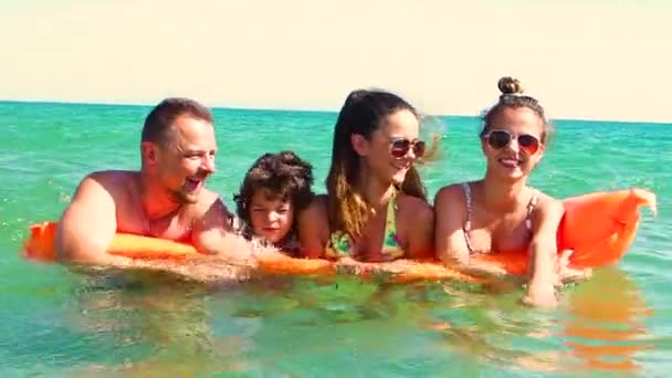 Happy family of four in vacation at sea shore. Happy family with yellow mattress bathes in sea. happy mum daddy and two children play in water. Slow Motion