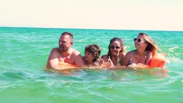 Zpomalený pohyb rodiny s oranžovou matrace baví v moři ve dne