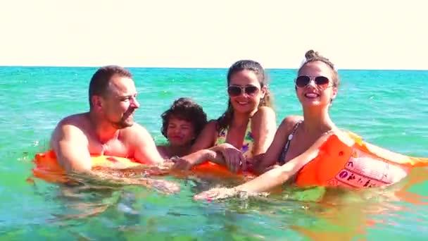 Šťastná rodina s oranžové matrace plavání v moři ve dne, cestování koncepce