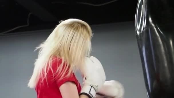 Schönes blondes Boxer-Training mit Boxsack im Fitnessstudio