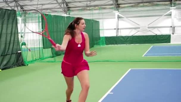 Krásná mladá žena v sportovním oblečení hrající tenis na tenisový kurt, pomalý pohyb