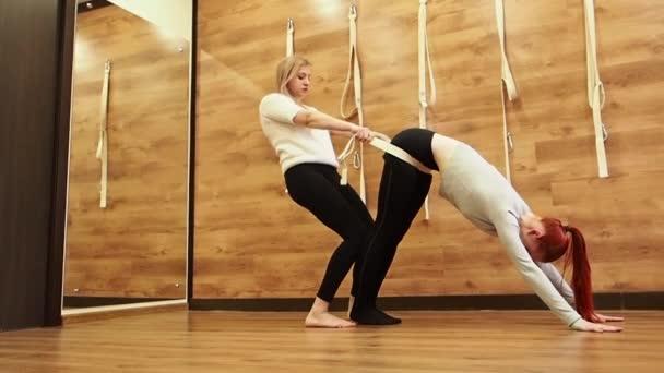 Dvě mladé ženy dělají v tělocviku cvičení jóga. Zpomaleně