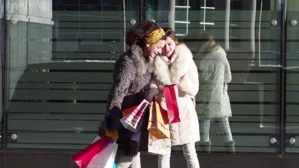 Dvě dívky v zimních šatech, které hledají nákupy po nakupování, moderní zázemí města. Zpomaleně