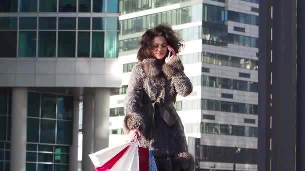 Mladá kudrnatá dívka v zimních šatech, která mluví ve dne na smartphone, moderní městské zázemí. Zpomaleně