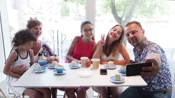 Mather, father, two daughters and little son having fun at coffee shop interior, slow motion