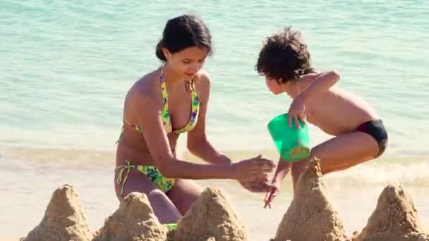 ältere Schwester spielt tagsüber mit kleinem Bruder am Sandstrand