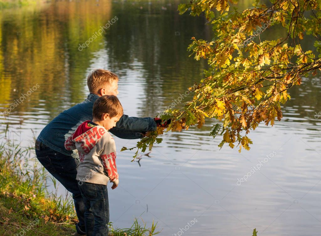 Two boys walking in the autumn park playing near water