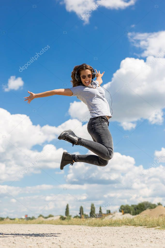 Beautiful young woman jumping in the air with headphones outside