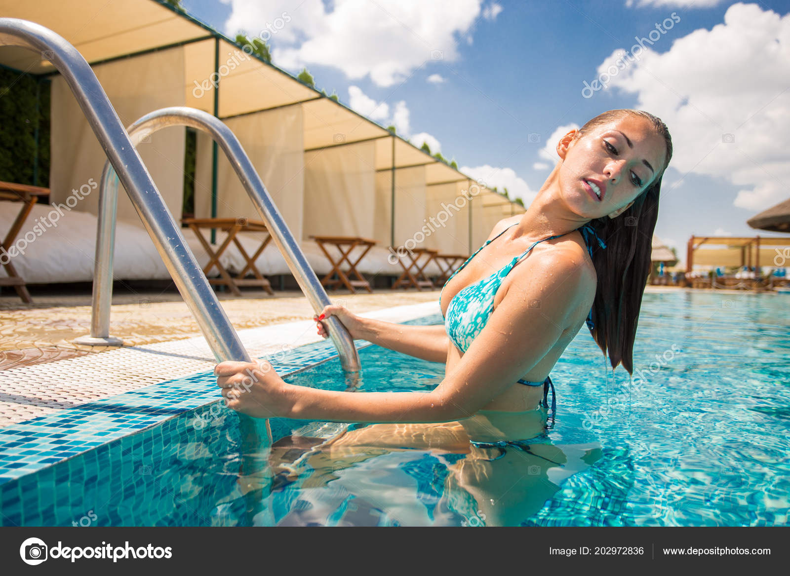 dfcffa40a06 Beautiful young woman stepping out of a swimming pool while smiling– stock  image