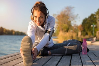 Beautiful young woman working out outside by the water while smiling