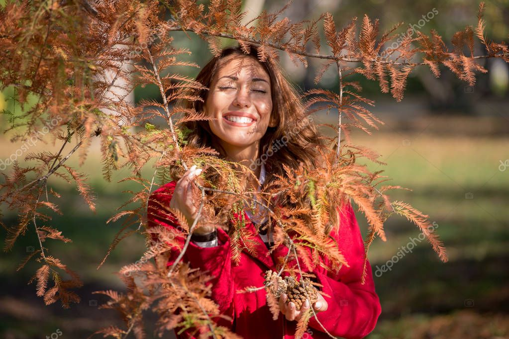 Beautiful young woman smiling behind an autumn tree
