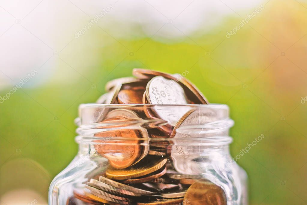 Coins in the glass jar against blurred green natural background for save money, business and finance concept