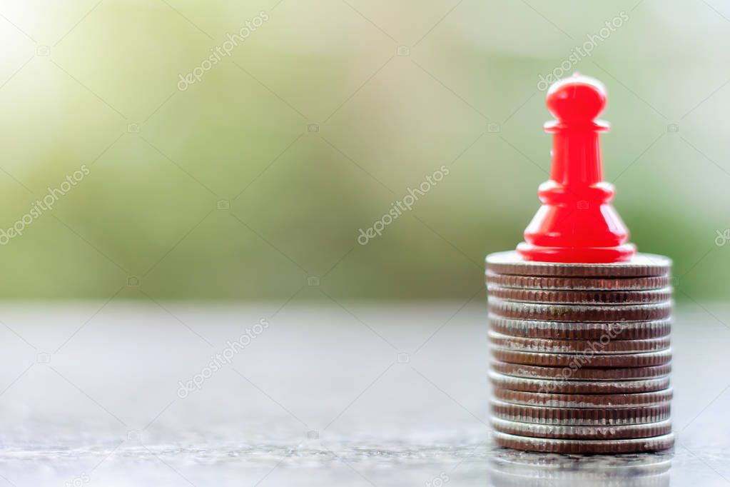 A red chess pawn on the stack of coins against blurred natural green background for investment and business strategy concept