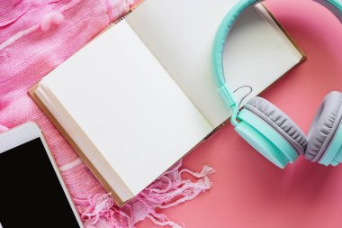 Opened notebook with headphones and smartphone on pink scarf