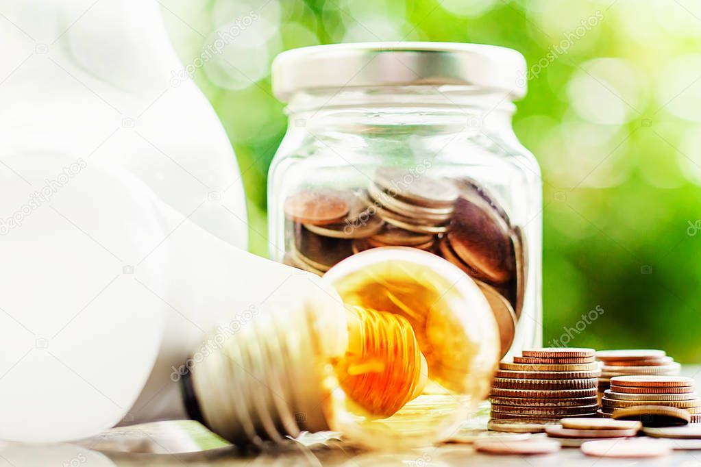 Glowing light bulb and led lamp with money coins in the glass jar against blurred natural green background for finance, saving energy and environment concept