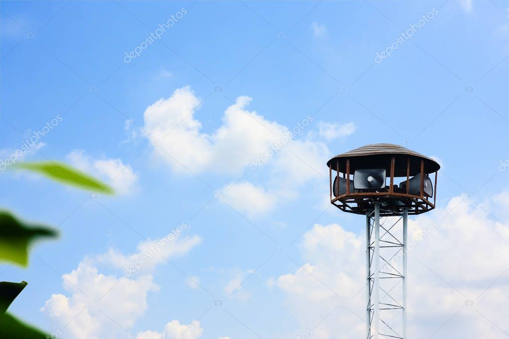 Public speaker tower against cloudy and blue sky background for announcements and alarms