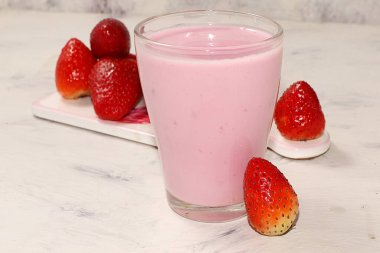 Strawberry smoothie fresh berries strawberries pink sunny background. The concept of healthy and natural food. Healthy breakfast, food for children, selective focus,