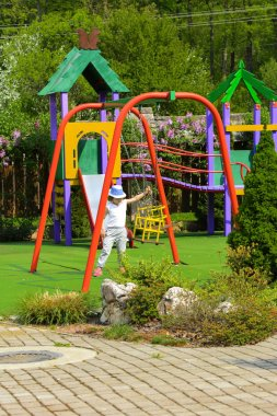 Little children run around and play in the playground. Game center for a young child. Little girl is playing outdoors. The concept of summer children's entertainment.