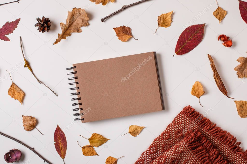 Autumn composition: fallen leaves, dry plants. scarf, brown craft sketchbook mock up on white background. Top view. Flat lay.