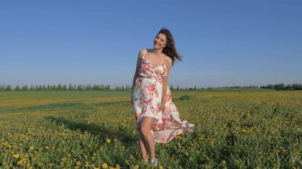 Portrét usmívající se žena stojící v rozkvetlých žlutých polí v šatech