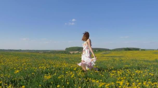 glücklich lächelnde Frau in schönem Kleid tanzt im blühenden gelben Feld